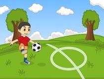 踢在公园动画片的孩子足球 免版税库存照片