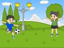 踢在公园动画片的孩子足球 免版税库存图片