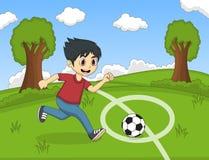 踢在公园动画片的孩子足球 免版税图库摄影