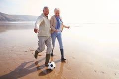 踢在冬天海滩的资深夫妇橄榄球 免版税库存照片
