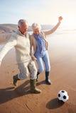 踢在冬天海滩的资深夫妇橄榄球 免版税库存图片