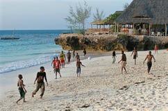 踢在印地安人Oce岸的非洲少年海滩橄榄球  免版税库存图片