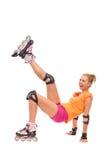 踢在天空中的女性rollerblader。 库存照片