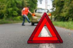 踢在残破的汽车的恼怒的司机轮胎 免版税库存照片