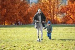 踢在沥青的父亲和儿子橄榄球 库存图片
