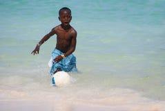 踢在海滩的年轻黑人男孩橄榄球 免版税图库摄影