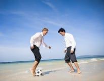 踢在海滩的两个商人橄榄球 免版税库存图片