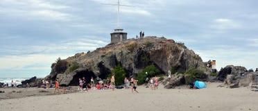 踢在海滩的人们足球在洞岩石,克赖斯特切奇 免版税图库摄影