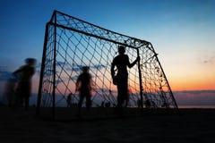 踢在海滩的男孩橄榄球在夏天 库存图片