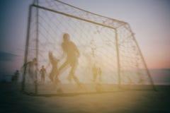踢在海滩的男孩橄榄球在夏天 库存照片