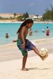 踢在海滩的男孩橄榄球在巴巴多斯 免版税图库摄影