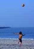 踢在海滩的男孩足球 免版税库存图片
