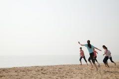 踢在海滩的年轻朋友足球 免版税库存照片