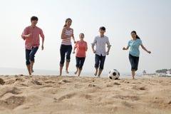 踢在海滩的年轻朋友足球 免版税库存图片