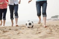 踢在海滩的年轻朋友足球 图库摄影