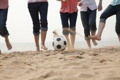 踢在海滩的年轻朋友足球 库存照片