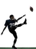 美国橄榄球运动员踢剪影的人喷射器 库存图片