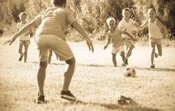 踢在草甸的孩子橄榄球 免版税库存照片