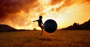 踢在草甸的小男孩橄榄球 库存照片