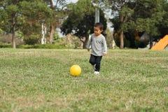 踢在草的日本男孩一个黄色球 免版税库存照片