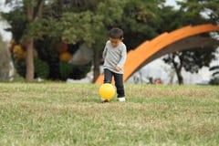 踢在草的日本男孩一个黄色球 免版税库存图片
