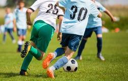 踢在草的男孩足球比赛 青年孩子的橄榄球赛 免版税库存照片