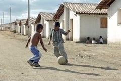 踢在街道的拉丁美州的男孩橄榄球,尼加拉瓜 免版税库存图片