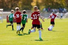 踢在运动场的男孩橄榄球 一个小组的行动体育图片打足球橄榄球比赛的孩子 免版税库存照片