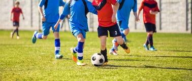 踢在运动场的年轻男孩足球运动员橄榄球 库存图片