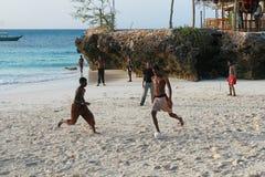 踢在银行印度洋的非洲十几岁海滩橄榄球 库存图片