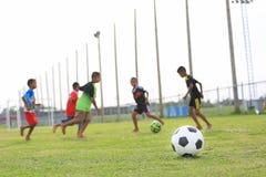 踢在领域的孩子橄榄球 免版税库存照片
