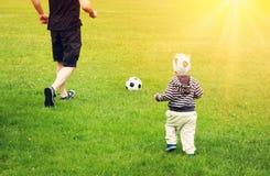 踢在领域的小男孩橄榄球与门 库存照片
