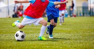 踢在绿草沥青的年轻男孩足球 橄榄球赛 免版税库存照片