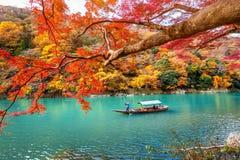 踢小船的船员在河 在秋天季节的Arashiyama沿河在京都,日本 免版税库存照片