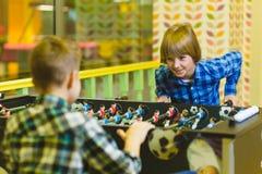 踢桌橄榄球的愉快的男孩在儿童居室 免版税库存照片