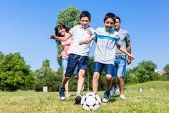 踢橄榄球或足球的家庭在公园在夏天 图库摄影