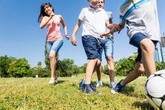 踢橄榄球或足球的家庭在公园在夏天 免版税库存照片
