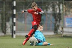 踢橄榄球或足球的小孩 免版税库存图片