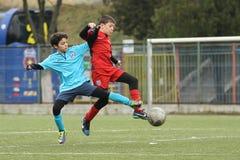 踢橄榄球或足球的小孩 免版税图库摄影