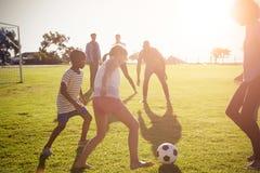 踢橄榄球的两个家庭在公园 图库摄影
