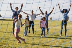 踢橄榄球的两个家庭在欢呼女孩的公园 免版税库存照片