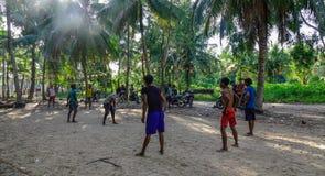 踢橄榄球的亚裔人在乡下 库存照片