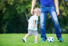 踢橄榄球的人和小孩儿子在公园 免版税库存图片