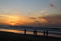 踢橄榄球的人们在海滩在巴西在日落期间 图库摄影