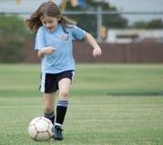 踢橄榄球的女孩 免版税库存照片