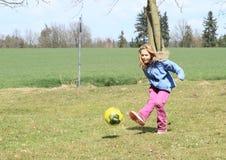 踢橄榄球的女孩 库存图片