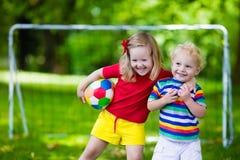 踢橄榄球的孩子在公园 免版税库存图片