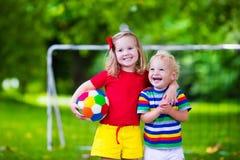 踢橄榄球的孩子在公园 免版税图库摄影