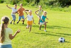 踢橄榄球的孩子在公园 免版税库存照片