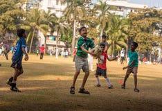 踢橄榄球的孩子在孟买地面 免版税库存照片